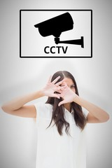 Composite image of fearful brunette covering her face