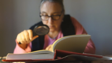 senior lady reading a book with a magnifier