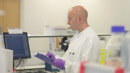 Portrait of male scientist making notes in Laboratory and looking at camera