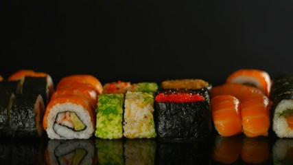 Fresh sushi on black table in motion