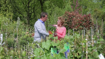 Mature couple looking at plants in garden centre