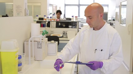 Male scientist looking at tube and making notes in Laboratory