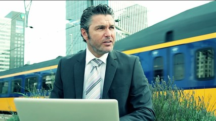 Business male working on laptop at train station