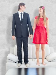 Geeky couple standing hand in hand on the couch