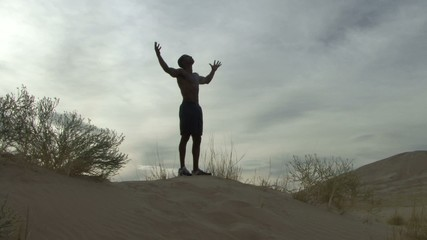 Male reaching his arms out in the desert