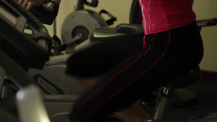 Female work out on bicycle in a gym