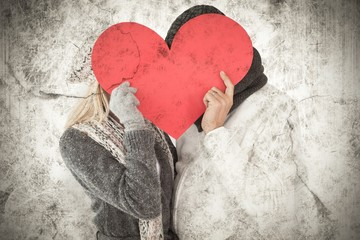 Couple in winter fashion posing with heart shape