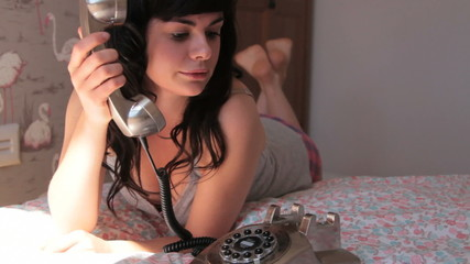 Female picking up phone and speaking in bedroom
