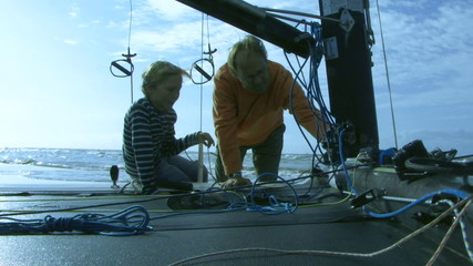 MS, Father giving son instructions on sailboat