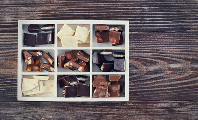 box with set of dark and milk chocolate on wooden table