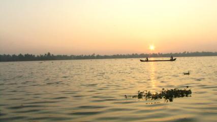 WS, Fisherman in boat on backwaters at sunset, Cochin, Kerala, India
