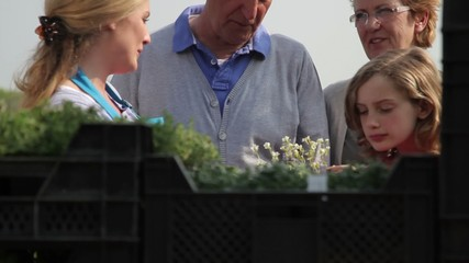 Garden centre employee showing Grandparents, and granddaughter plants in garden centre