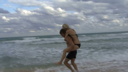 Couple running and playing on a beach