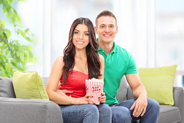 Couple sitting on a sofa with a box of popcorn