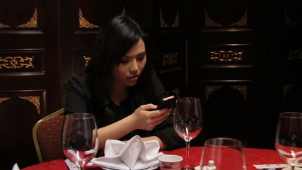 Female in restaurant looking at mobile whilst waiting for date