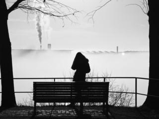 depressive Frau im Nebel allein vor der Parkbank stehend