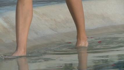 CU PAN OF A WOMAN WALKING THROUGH WATER