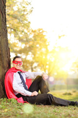 Joyful man in superhero outfit sitting in a park