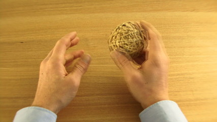 OS, WS, Time lapse, Male playing with ball made of elastic bands on desk