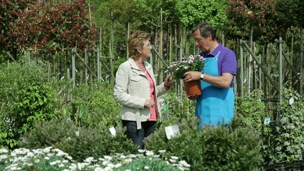 Mature male handing over plant to female in garden centre