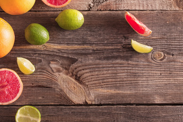 Set of sliced citrus fruits over wooden background