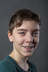 portrait of a smiling teenage boy, with gray background for fast