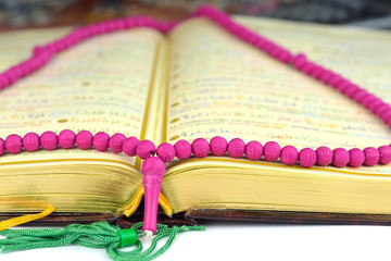 Close up of a Holy Koran with a rosary praying beads