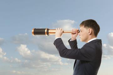 Businessman looks through a telescope