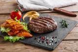burger grill with vegetables and sauce on a wooden surface