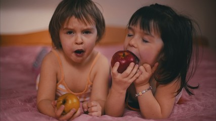 Two Girls are Eating an Apple