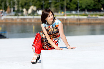 Model in dress posing on exterior set sitting