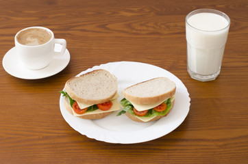 cup of coffee, glass a milk and sandwiches