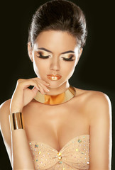Golden Makeup. Fashion beautiful young girl in luxurious beige d
