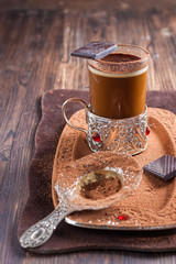 coffee with chocolate in a glass cup holder on a metal tray