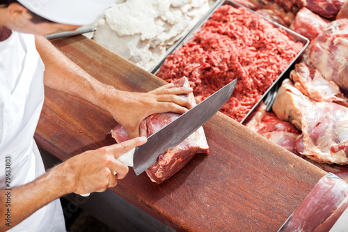 Smiling Butcher Cutting Meat At Counter - 79633803