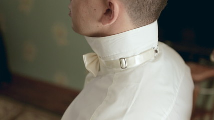 Young stylish groom puts bow-tie on shirt