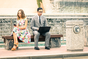 Couple in moment of disinterest with laptop and smartphone