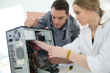 Teacher with student in technology repairing computer