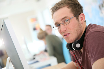 Student with eyeglasses sitting in front of desktop