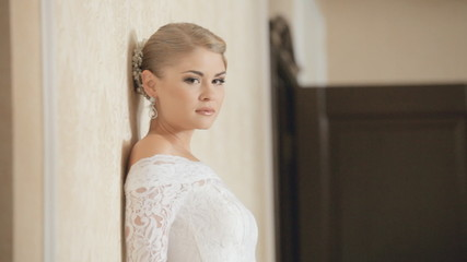 Glamourous bride posing on the background of wall indoors