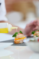 Closeup of olive oil being poured over appetizer
