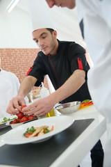 Chef training students in restaurant kitchen