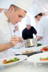 Young cook pouring sauce on dish