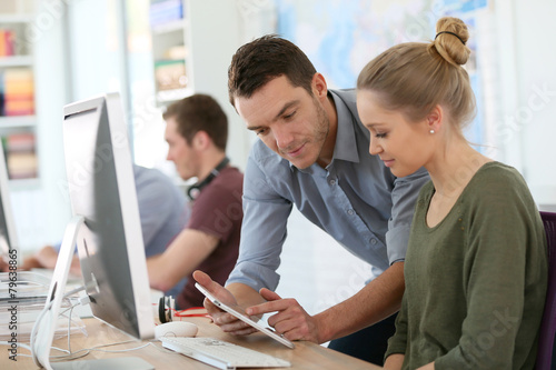 Student girl with trainer working on computer and tablet