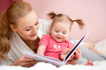 happy mother read a book to baby girl