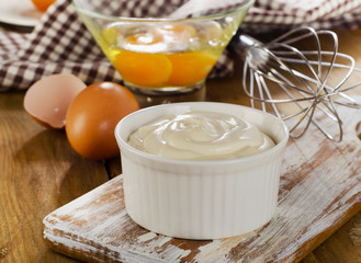 Mayonnaise in  bowl with eggs  on a wooden background