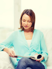 smiling woman reading magazine at home