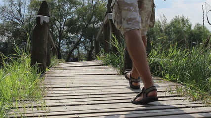 Man Steps Across a Footbridge