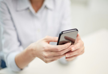 close up of woman texting on smartphone at office
