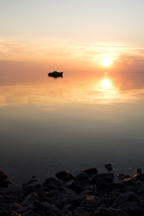 silhouette of a floating boat at sunset